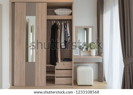 modern closet with clothes hanging on rail, white wooden wardrobe, interior design concept #1233108568