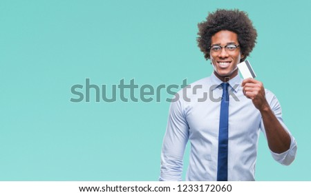 Afro american man holding credit card over isolated background with a happy face standing and smiling with a confident smile showing teeth