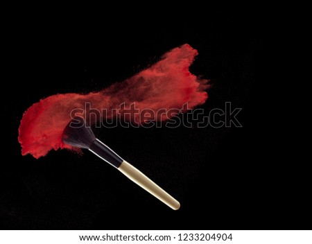 Make-up brush with red powder explosion on black background #1233204904