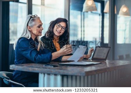Two women analyzing documents while sitting on a table in office. Woman executives at work in office discussing some paperwork. #1233205321
