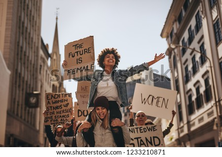 Group of female protesters marching on the road with signboards and smiling. Women holding protest banners and marching outdoors. #1233210871