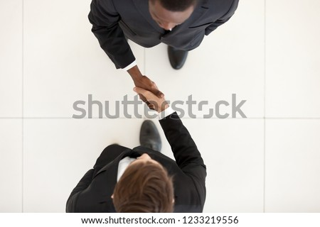 Two diverse businessmen shaking hands in office, black and white partners greeting with handshake as respect concept, collaboration deal, support, business acquaintance, first impression, top view #1233219556
