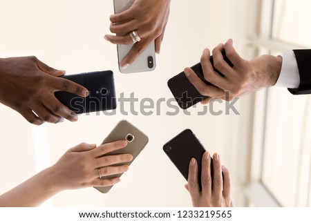 Male and female diverse hands holding cell phones, multiracial business people using smartphones applications software, users and devices concept, mobile communication, close up below bottom view Royalty-Free Stock Photo #1233219565