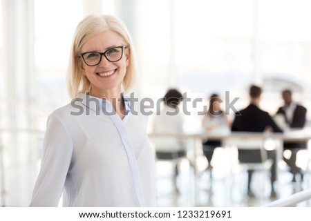 Smiling mature attractive businesswoman in glasses looking in camera, happy friendly middle aged female executive, older team leader or business coach mentor posing in office, headshot portrait #1233219691