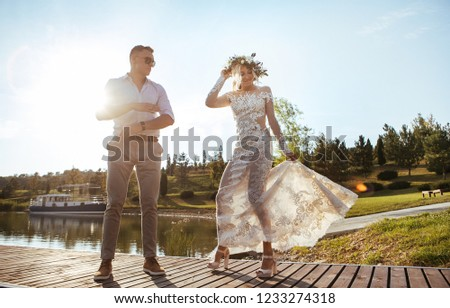 bride and groom in a wreath on her head and a vintage dress dancing against the backdrop of the lake at sunset #1233274318