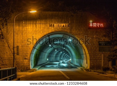 Tunnel, Toyama, Japan. TRANSLATION OF JAPANESE TEXT: use lights in tunnel; Asahi ogawa tunnel; keep your distance; length 1316m; emergency phones every 200m; call buttons, 50m; extinguishers, 50m. #1233284608