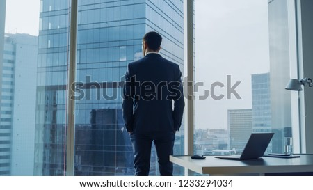 Back View of the Thoughtful Businessman wearing a Suit Standing in His Office, Hands in Pockets and Contemplating Next Big Business Deal, Looking out of the Window. Big City Business District View #1233294034