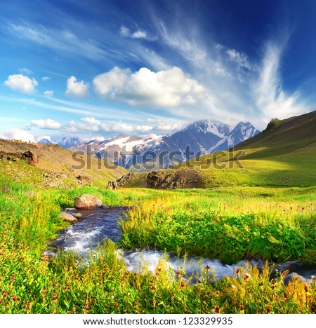 River on bright green meadow. High mountain and clouds. #123329935