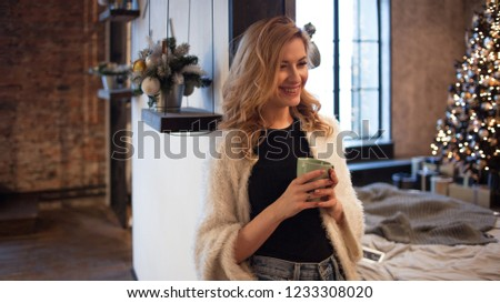 First day of the new year. Happy and confident young woman at home drinking morning coffee. the background of an apartment with a decorated Christmas tree #1233308020
