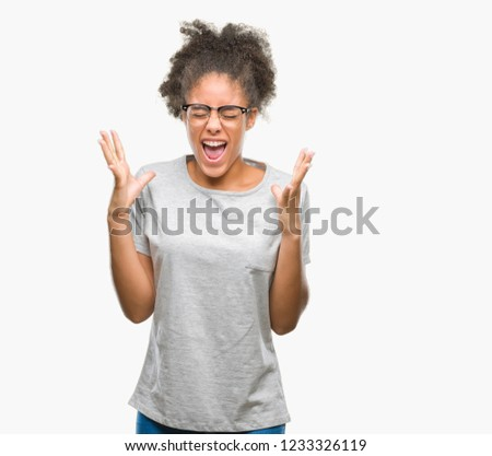 Young afro american woman wearing glasses over isolated background celebrating mad and crazy for success with arms raised and closed eyes screaming excited. Winner concept #1233326119
