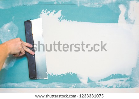 Hand with putty knife repair wall, Hand with a spatula, spatula with spackle paste structure, process of applying layer of putty trowel, working with spackling paste #1233331075