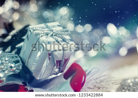Shiny silver Christmas gift box with falling winter snowflakes and copyspace for your greeting or wishes
