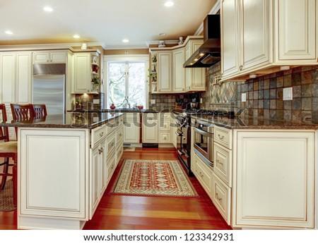 Large luxury white kitchen with cherry hardwood. #123342931