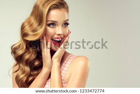 Woman with red lips and nails surprise holds cheeks by hand .Beautiful girl  with curly hair surprised and shocked looking on you . Presenting your product. Expressive facial expressions #1233472774