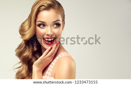 Woman with red lips and nails surprise holds cheeks by hand .Beautiful girl  with curly hair surprised and shocked   looking  aside . Presenting your product. Expressive facial expressions  #1233473155