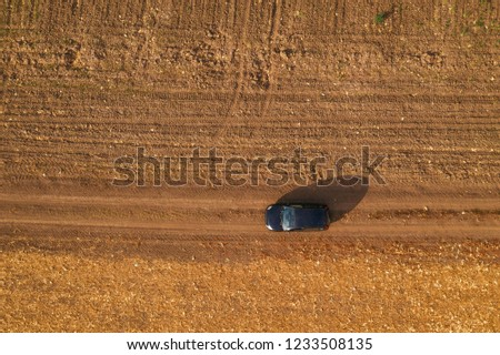 Aerial view of black car on dirt road through countryside, top view of off-road driving vehicle from drone pov #1233508135