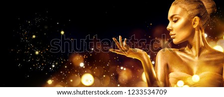 Gold Christmas Woman. Beauty fashion model girl with Golden make up, hair and jewellery, pointing hand on black background. Gold glowing skin. Metallic, glance Fashion art portrait, Hairstyle, make up #1233534709
