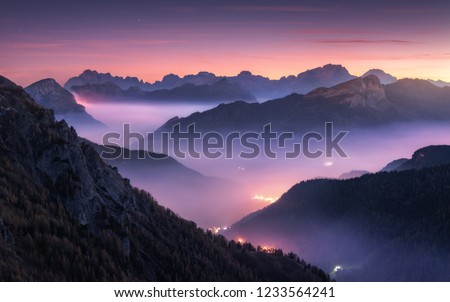 Mountains in fog at beautiful night in autumn in Dolomites, Italy. Landscape with alpine mountain valley, low clouds, forest, purple sky with stars, city illumination at sunset. Aerial. Passo Giau #1233564241