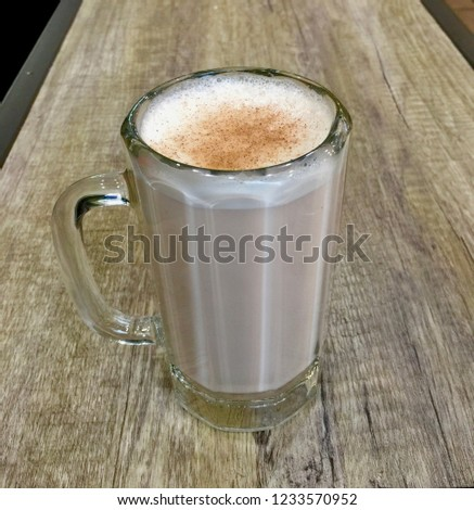 Latte with cinnamon in tall glass on wooden table #1233570952