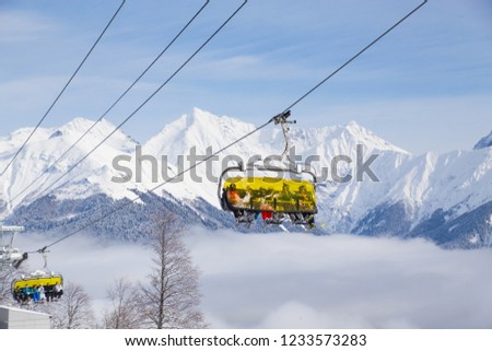 sports people on the chairlift in a ski resort among snow-capped mountains #1233573283