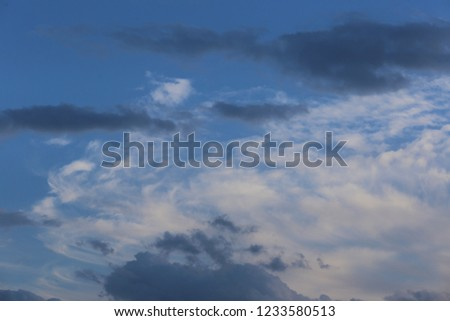 View of a cloudy sky during a sunny afternoon in France, during the autumn season. White and grey lighted clouds with a blue natural background. Abstract picture of space, #1233580513