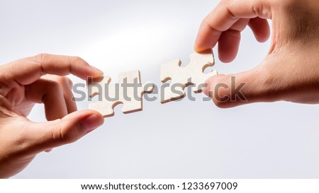 Pieces of jigsaw puzzle in woman's hands #1233697009