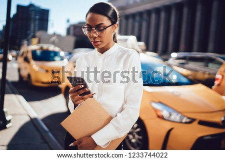 Young African American woman reading interesting network content in newspaper application on telephone while waiting for yellow cab on city street. Female calling taxi car via smartphone app service #1233744022