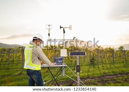 Agronomist using tablet computer collect data with meteorological instrument to measure the wind speed, temperature and humidity and solar cell system in grape agricultural field, Smart farm concept #1233854140