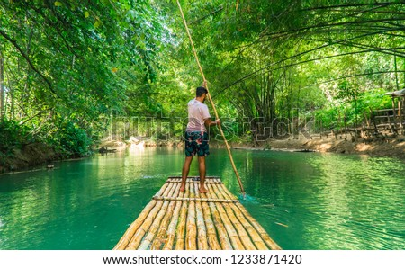 Landscape shot of man (tourist) rowing bamboo raft, whilst on cruise on vacation in Montego Bay, Jamaica, Caribbean. Martha Brae 2019. #1233871420