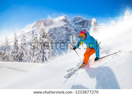 Skier skiing downhill during sunny day in high mountains #1233877270