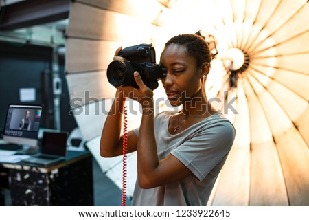 Young photographer standing in front of a reflective umbrella Royalty-Free Stock Photo #1233922645