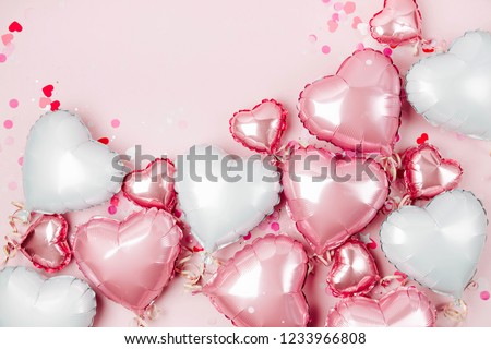 Air Balloons of heart shaped foil  on pastel pink background. Love concept. Holiday celebration. Valentine's Day or wedding/bachelorette party decoration. Metallic balloon #1233966808