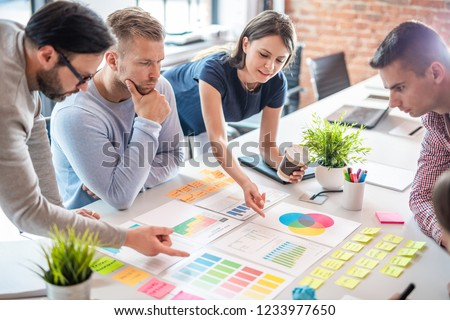 Business people meeting at office and use post it notes to share idea. Brainstorming concept. Sticky note on glass wall. #1233977650