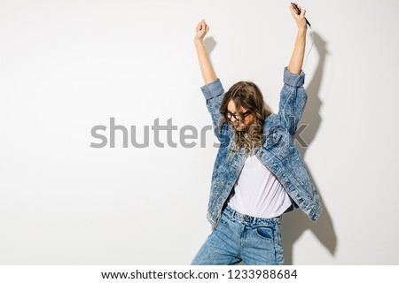 listen to the music and dance. concept with a young expressive beautiful woman in retro jeans outfit listening music with headphones and dancing, on white background #1233988684