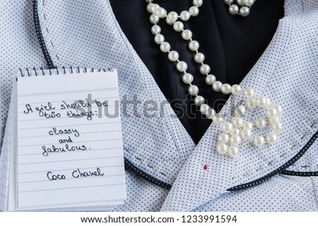 "Coco Chanel quotes written on a block note, pearl accessories and a classy jacket ,inspiration phrase ""A girl should be two things: classy and fabulous"""