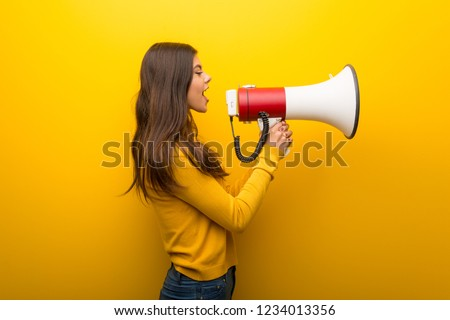 Teenager girl on vibrant yellow background shouting through a megaphone to announce something in lateral position #1234013356