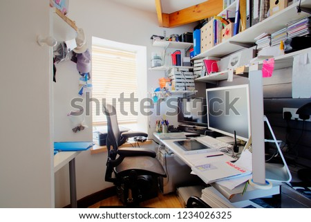 A shot of a messy desk in a home office, the room is small and cluttered, on the desk is three computer monitors and office supplies. Royalty-Free Stock Photo #1234026325
