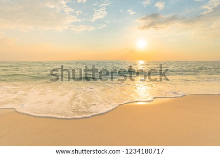 Soft sea waves and bubbles on the beach with sunset sky background. Royalty-Free Stock Photo #1234180717