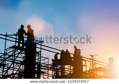 Silhouette of engineer and construction team working at site over blurred background for industry background with Light fair. #1234319017