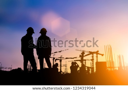 Silhouette of engineer and construction team working at site over blurred background for industry background with Light fair. #1234319044