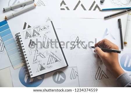 Graphic designer drawing sketch design creative Ideas draft Logo product trademark label brand artwork. Graphic designer studio Concept. #1234374559