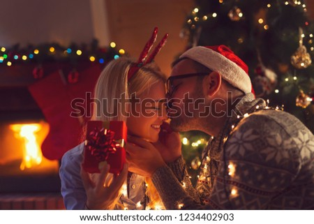 Young couple in love sitting by the fireplace and nicely decorated Christmas tree, exchanging Christmas presents #1234402903