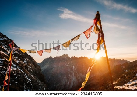 Peaceful praying flags fluttering on the wind in Rysy winter mountain at sunset in Slovakia #1234415605