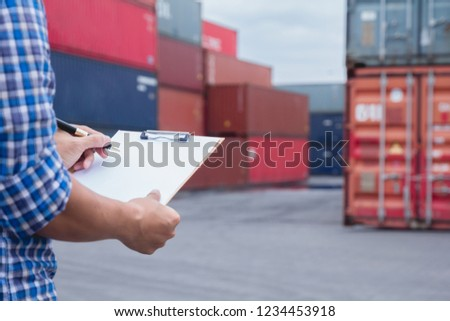 Man taking note checking cargo shipping at container yard area.Worker man signing papers about import - export logistic business.