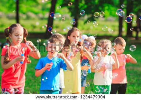 Group of children blowing soap bubbles #1234479304