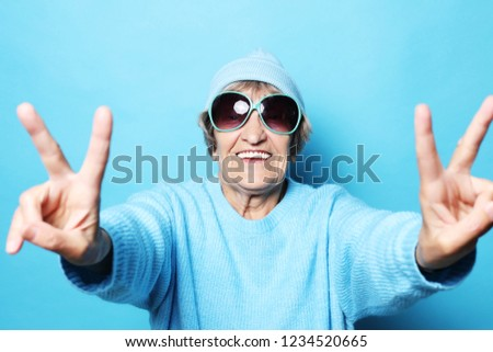 Lifestyle, emotion  and people concept: Funny old lady wearing blue sweater, hat and sunglasses showing victory sign. Isolated on blue background. #1234520665