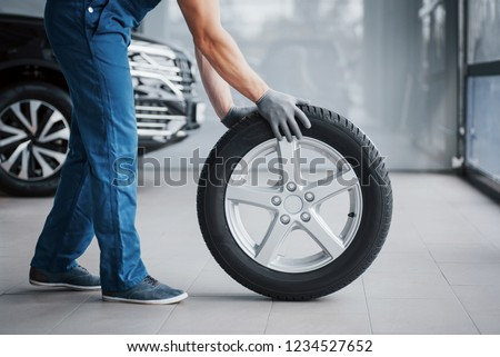 Mechanic holding a tire tire at the repair garage. replacement of winter and summer tires. #1234527652