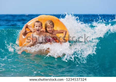 Happy kids have fun in sea surf on beach. Joyful couple of children on inflatable ring ride on breaking wave. Travel lifestyle, swimming activities in family summer camp. Vacations on tropical island  #1234537324