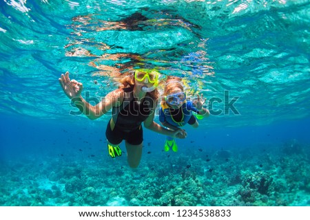 Happy family - mother, kid in snorkeling mask dive underwater with tropical fishes in coral reef sea pool. Show by hands divers sign OK. Travel lifestyle, beach adventure on summer holiday with child. #1234538833