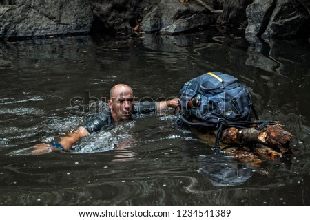 A man is swimming in a river and at the same time supporting a hand-made improvised raft with his backpack. Concept of survival and exploration in the wild. Man vs wild. #1234541389